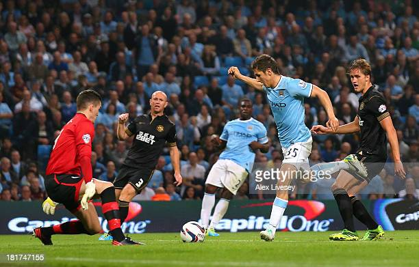 Stevan Jovetic of Manchester City scores the second goal past Lee Nicholls of Wigan Athletic during the Capital One Cup third round match between...