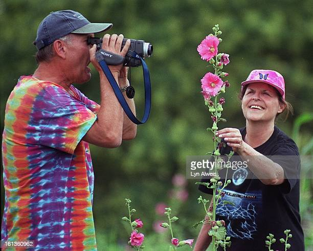 Steve and Nancy Seaver check out the pink hollyhock plant at the Denver Botanic Gardens' Community Garden The couple are school teachers rom Miami...