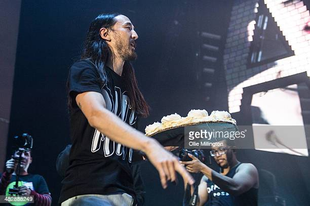 Steve Aoki performs throwing a cake into the crowd onstage during a date of his Neon Future tour at Brixton Academy on April 4 2014 in London England