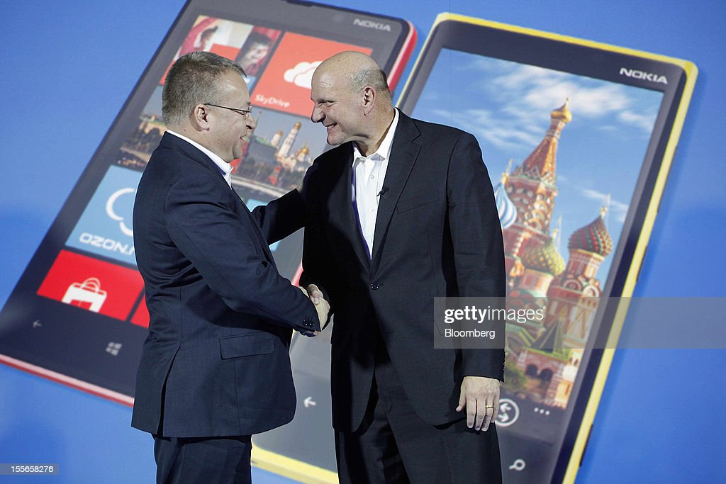 Steve Ballmer, chief executive officer of Microsoft Corp., right, and Stephen Elop, chief executive officer of Nokia Oyj, shake hands after a presentation of the new Nokia Lumia 920 smartphone at a news conference in Moscow, Russia, on Tuesday, Nov. 6, 2012. Microsoft is considering building mobile hardware as a backup, in the event that its current approach of providing software to handset makers such as Nokia Oyj and HTC Corp. falters, said the people, who requested anonymity because the plans are private. Photographer: Alexander Zemlianichenko Jr./Bloomberg via Getty Images