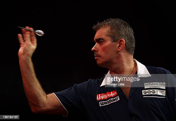 Steve Beaton of England throws against Simon Whitlock of Australia during Day 11 of the 2012 Ladbrokescom World Darts Championship at Alexandra...