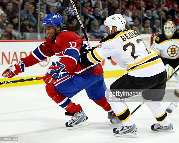 Steve Begin of the Boston Bruins body checks Georges Laraque of the Montreal Canadiens during the NHL game on December 4 2009 at the Bell Centre in...
