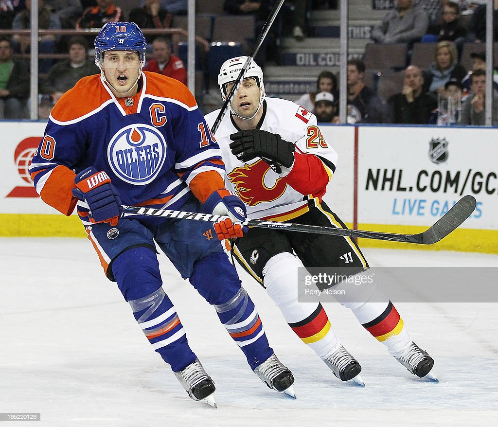 Steve Begin #25 of the Calgary Flames looks for a puck against Shawn Horcoff #10 of the Edmonton Oilers at Rexall Place on April 1, 2013 in Edmonton, Alberta, Canada.