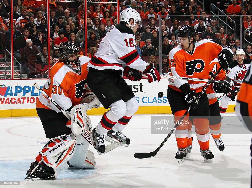 Steve Bernier #18 of the New Jersey Devils attempts to screen goaltender Ilya Bryzgalov #30 of the Philadelphia Flyers while Luke Schenn #22 of the Flyers blocks the shot on March 15, 2013 at the Wells Fargo Center in Philadelphia, Pennsylvania. The Flyers went on to defeat the Devils 2-1 in a shoot-out.