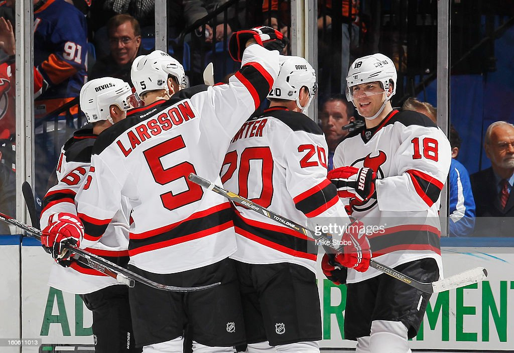 Steve Bernier #18 of the New Jersey Devils is congratulated by his teamates after his goal against the New York Islanders at Nassau Veterans Memorial Coliseum on February 3, 2013 in Uniondale, New York. The Devils defeated the Islanders 3-0.
