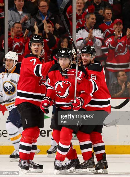 Steve Bernier of the New Jersey Devils is congratulated by teammates Mark Fayne and Andy Greene after Bernier scored the game winning goal in...