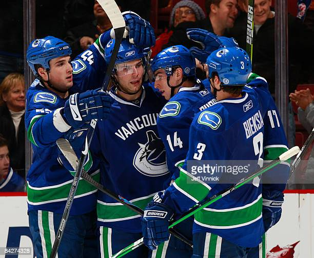 Steve Bernier of the Vancouver Canucks is congratulated by teammates Shane O'Brien Alex Burrows and Kevin Bieksa after scoring against the New Jersey...