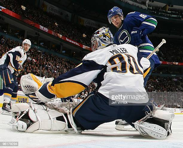 Steve Bernier of the Vancouver Canucks is stopped in close by Ryan Miller of the Buffalo Sabres as Henrik Tallinder looks on during their game at...
