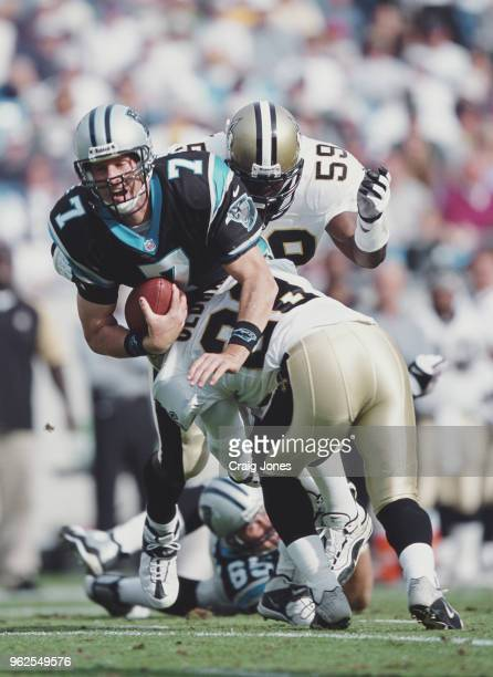 Steve Beuerlein Quarterback for the Carolina Panthers is sacked by Chris Oldham Defensive Back for the New Orleans Saints during their National...
