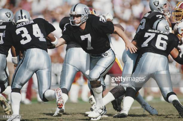 Steve Beuerlein, Quarterback for the Los Angeles Raiders hands off to running back Bo Jackson during their National Football Conference West game...