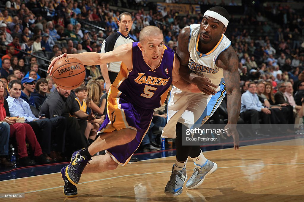 Steve Blake #5 of the Los Angeles Lakers controls the ball against Ty Lawson #3 of the Denver Nuggets at Pepsi Center on November 13, 2013 in Denver, Colorado.
