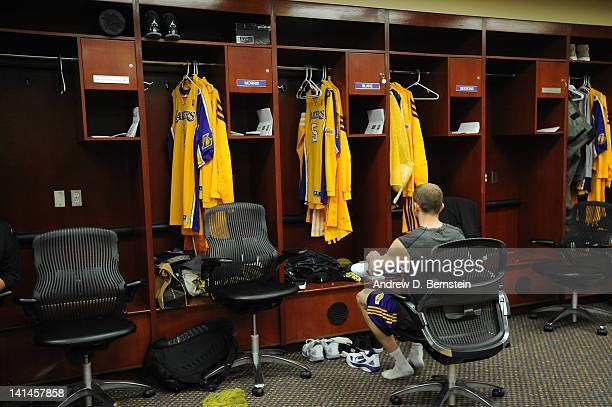 Steve Blake of the Los Angeles Lakers gets dressed in the locker room near the empty locker of former teammate Derek Fisher before a game against the...