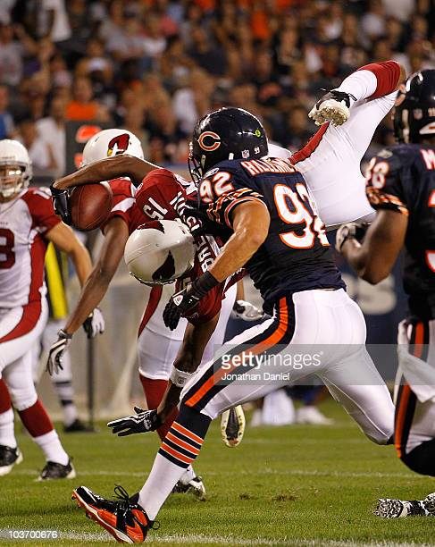 Steve Breaston of the Arizona Cardinals dives in to the end zone for a touchdown as Hunter Hillenmeyer of the Chicago Bears pursues during a...