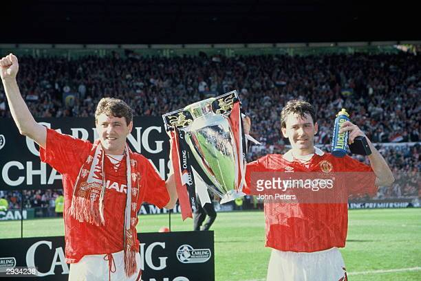 Steve Bruce and Bryan Robson of Manchester United lift the Premiership Trophy after becoming FA Carling Premiership Winners in the 199394 season at...
