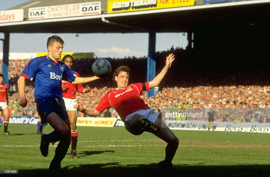 Steve Bruce (right) of Manchester United falls back during the FA Cup Semi-Final against Oldham at Maine Road in Manchester, England. The match ended in a 3-3 draw. \ Mandatory Credit: Simon Bruty/Allsport