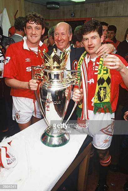 Steve Bruce Sir Bobby Charlton and Denis Irwin celebrate with the Premiership Trophy in the dressing room after the FA Carling Premiership Match...