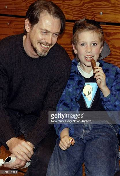 Steve Buscemi sits with his son Lucien at charity basketball game at Hunter College Buscemi was the master of ceremonies at the event sponsored by...