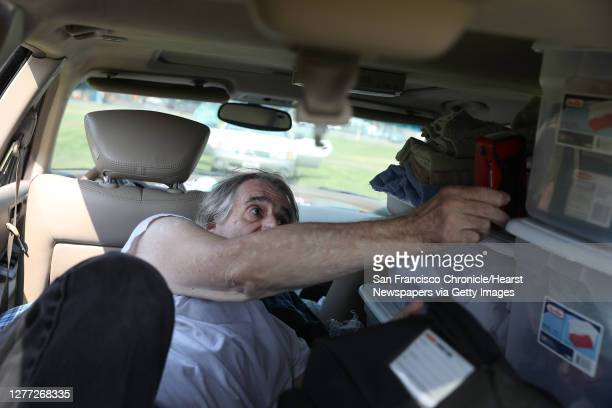 Steve Casa of Santa Rosa holds a Red Cross hand crank radio as he lays in his car at an evacuation center at the Sonoma Marin Fairgrounds and Event...
