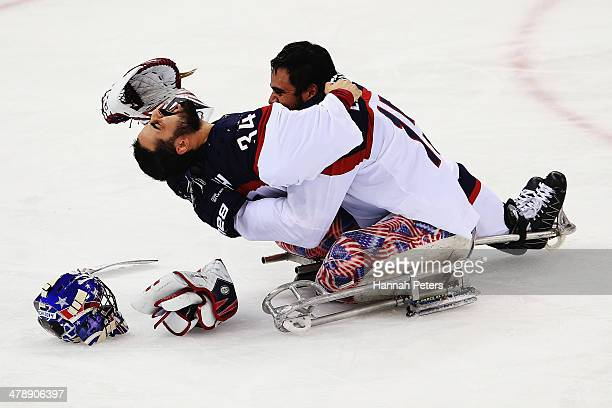 Steve Cash of the USA and Nikko Landeros of the USA celebrate after winning the ice sledge hockey gold medal game between the Russian Federation and...