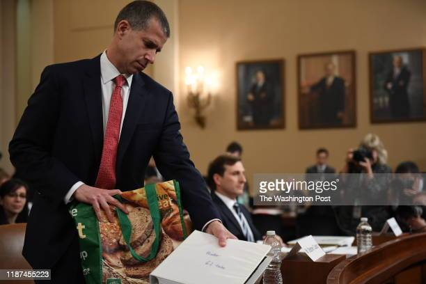 Steve Castor removes a binder from a reusable shopping bag before the House Judiciary Committee about to hear evidence presented by the Democratic...