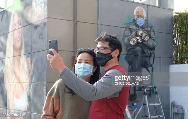 Steve Cho and Michelle Ching, who worked on Bernie Sanders 2016 campaign, take a selfie in front of artist Jonas Never mural of Senator Bernie...