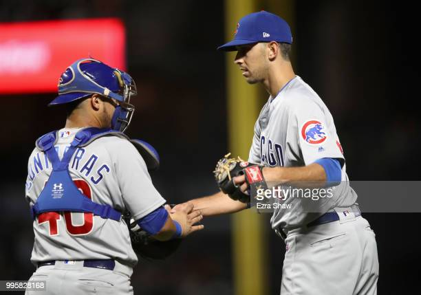 Steve Cishek of the Chicago Cubs shakes hands with Willson Contreras after they beat the San Francisco Giants at ATT Park on July 10 2018 in San...