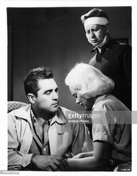 Steve Cochran holds the hands of Mamie Van Doren while Mel Tormé stands over them in a scene from the film 'The Big Operator', 1959.