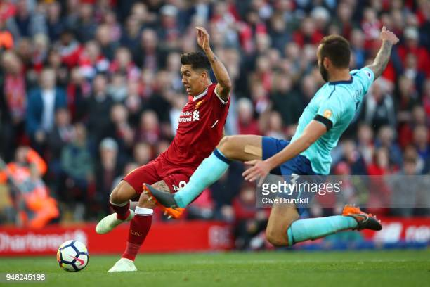 Steve Cook of AFC Bournemouth attempts to tackle Roberto Firmino of Liverpool during the Premier League match between Liverpool and AFC Bournemouth...
