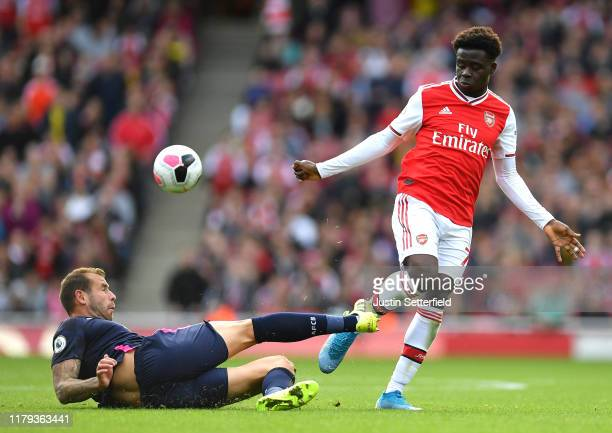 Steve Cook of AFC Bournemouth tackles Bukayo Saka of Arsenal during the Premier League match between Arsenal FC and AFC Bournemouth at Emirates...