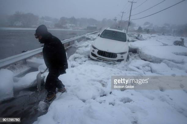 Steve Corsano investigates an abandoned vehicle trapped in sea ice on Bailys Causeway during the storm in Scituate Mass on Jan 04 2018