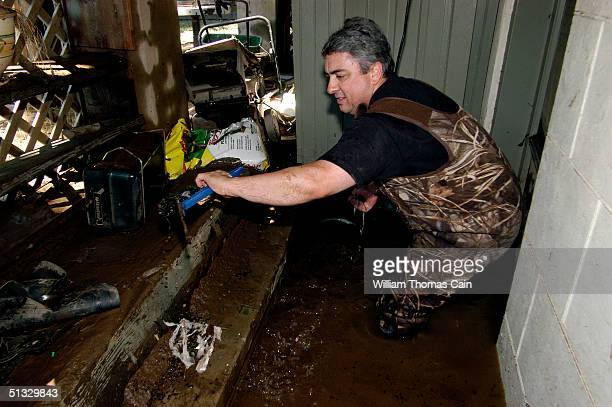 Steve Coyle clears debris from a sump pump after flood waters entered his basement September 20 2004 in Yardley Pennsylvania Rain from the remnants...