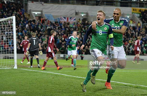 Steve Davis of Northern Ireland celebrates with team mate Josh MaGennis after scoring during the international football friendly match between...
