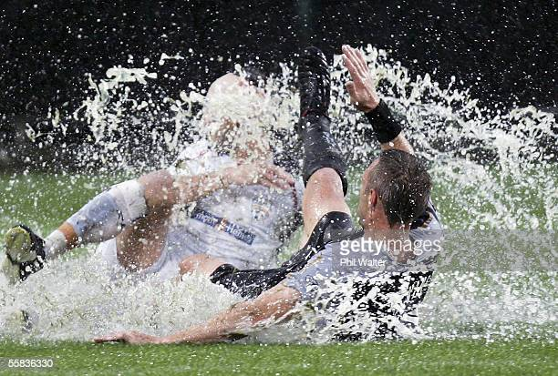 Steve Devine of the Knights and Michael Valkanis of Adelaide slide through the water following a tackle during the round six ALeague match between...