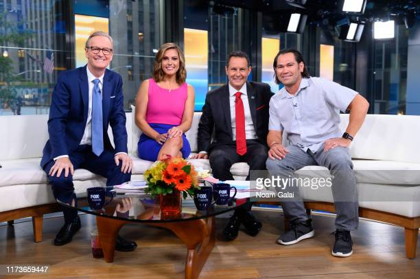 Steve Doocy Lisa Boothe Brian Kilmeade and Johnny Damon pose for a photo during FOX Friends at Fox News Channel Studios on September 10 2019 in New...