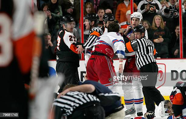 Steve Downie of the Philadelphia Flyers is separted by the Referees Brad Meier and Kelly Sutherland during a scrum against the New York Rangers as a...