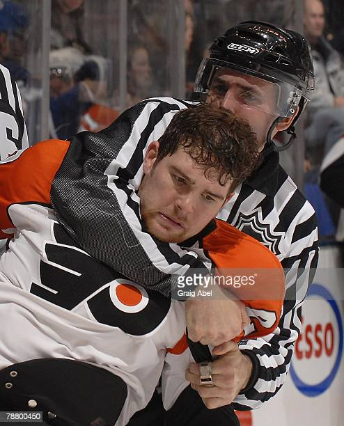 Steve Downie of the Philadelphia Flyers is wrestled to the ice by linesman Steve Miller during the game against the Toronto Maple Leafs January 5...