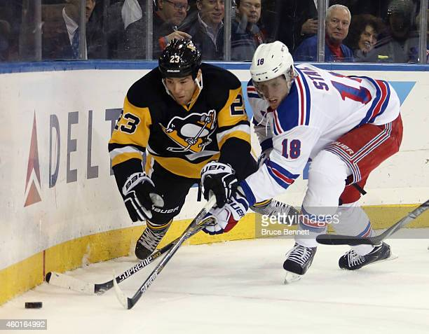 Steve Downie of the Pittsburgh Penguins is tripped up by Marc Staal of the New York Rangers during the first period at Madison Square Garden on...