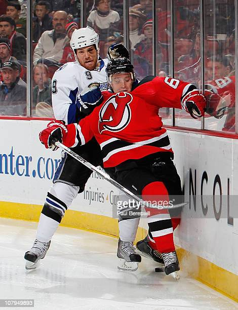 Steve Downie of the Tampa Bay Lightning takes down Andy Greene of the New Jersey Devils in the third period of an NHL hockey game at the Prudential...