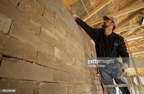 DENVER CO MARCH 27 2004 Steve Eagleburger of Denver puts the insulates between the wall and roof of his adobe house on Saturday Steve and his wife...