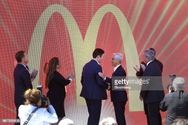Steve Easterbrook chief executive officer of McDonald's Corp center left shakes hands with Rahm Emanuel mayor of Chicago center right during the...