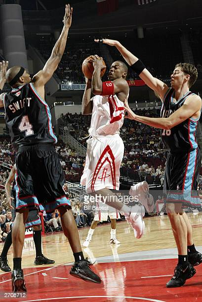 Steve Francis of the Houston Rockets shoots against Stromile Swift and Pau Gasol of the Memphis Grizzlies drives during the game at Toyota Center on...