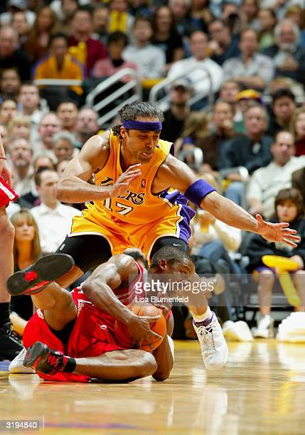 Steve Francis of the Houston Rockets tries to hold on to the ball under pressure from Rick Fox of the Los Angeles Lakers during the game at Staples...
