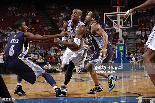 Steve Francis of the Orlando Magic drives to the basket while being defended by Damon Stoudamire and Eddie Jones of the Memphis Grizzlies during a...
