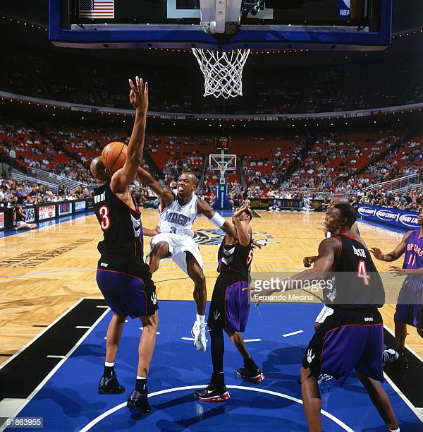 Steve Francis of the Orlando Magic looses the ball as he drives to the basket between Loren Woods and Vince Carter of the Toronto Raptors during a...