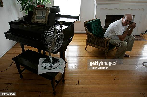 Steve Friedland wipes sweat from his brow as he tries to cope with two days of power outages and high temperatures at his Country Club Park home...