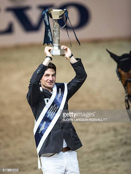Steve Guerdat of Switzerland celebrates with the trophy winning the Longines FEI World Cup Jumping Final event of the Gothenburg Horse Show at...