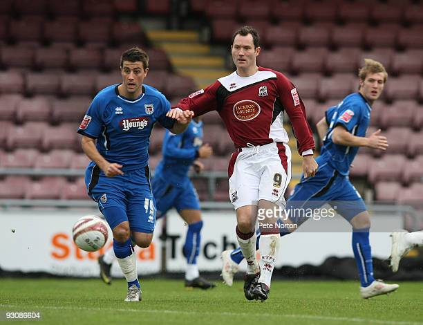Steve Guinan of Northampton Town plays the ball watched by Michael Leary of Grimsby Town during the Coca Cola League Two Match between Northampton...