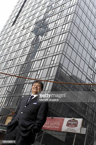 Steve Gupta President and CEO of Easton's Group of Hotels Inc standing in front of his newest projects at 255 Wellington St W CN Tower reflected in...