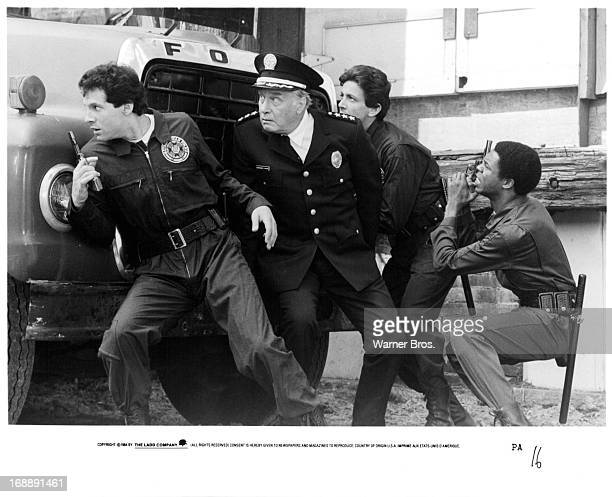 Steve Guttenberg George Gaynes Andrew Rubin and Michael Winslow pursue a criminal in a scene from the film 'Police Academy' 1984