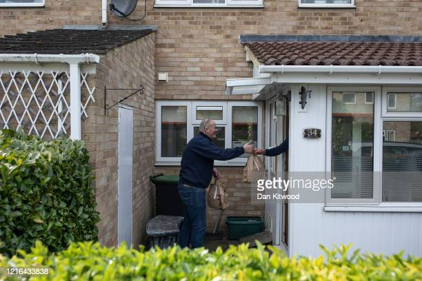 Steve Hammond, formerly of the 1st Battalion the Welsh Guards, hands out food parcels to elderly residents at the Royal British Legion village, while...